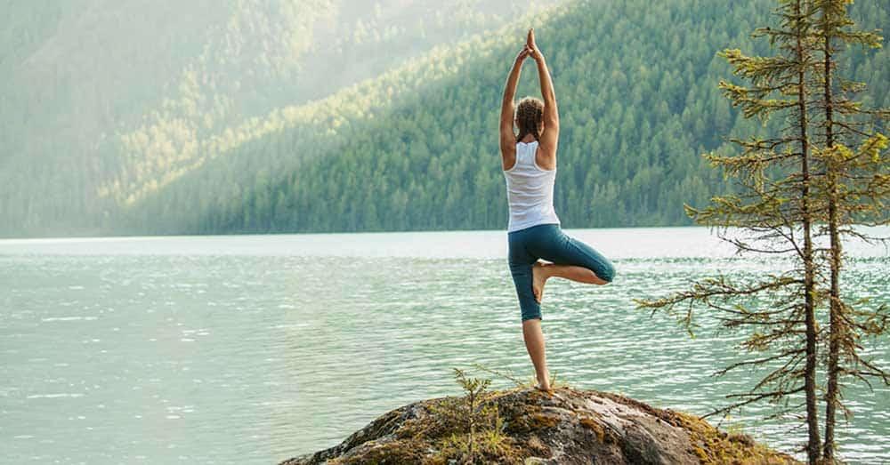 Junge Frau praktiziert Joga Fuße eines Bergsees und geniesst das Wasser